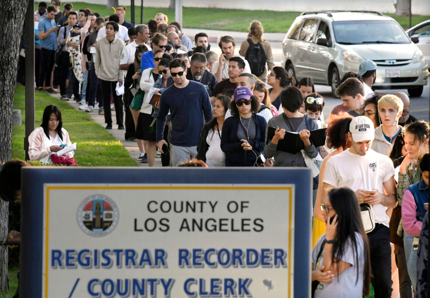 In this Nov. 6, 2018 file photo, potential voters wait in long lines to register and vote at the Los Angeles County Registrar's office in Los Angeles. A pair of propositions on California's November 2020 ballot would expand voting rights in California - restoring the vote for parolees and allowing 17-year-olds to vote in primaries if they turn 18 before the general election. (Source: AP Photo/Mark J. Terrill, File)